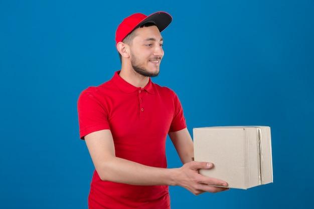 Jonge leveringsmens die rood poloshirt en glb draagt die kartondoos aan klant met glimlach op gezicht over geïsoleerde blauwe achtergrond geeft