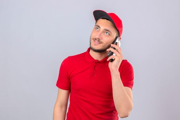 Jonge leveringsmens die rood poloshirt en glb draagt die op mobiele telefoon spreken die dromerig over geïsoleerde witte achtergrond kijken