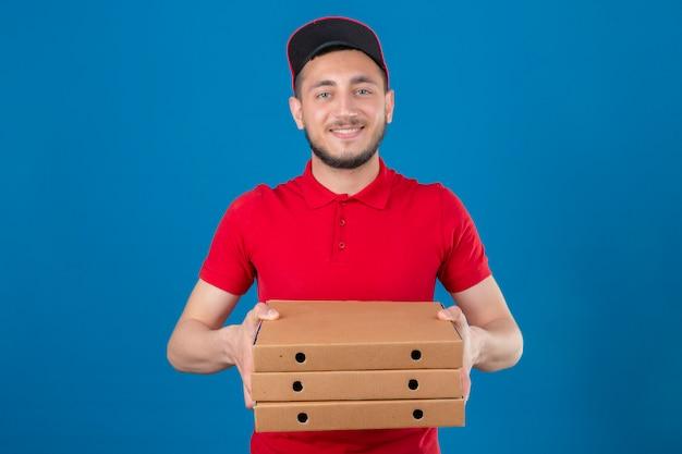 Jonge leveringsmens die rood poloshirt en glb draagt die stapel pizzadozen in handen toont die camera over geïsoleerde blauwe achtergrond bekijken glimlachen