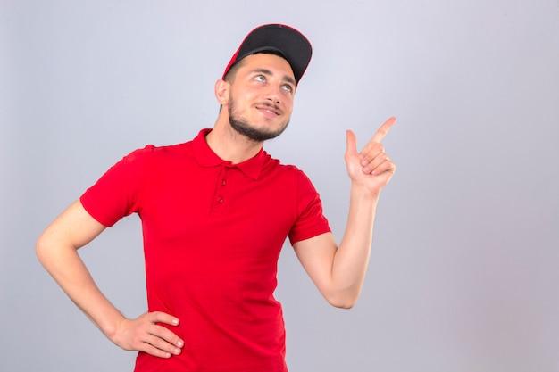 Jonge leveringsmens die rood poloshirt en glb draagt die vinger op exemplaarruimte richt die met glimlach op gezicht over geïsoleerde witte achtergrond kijken
