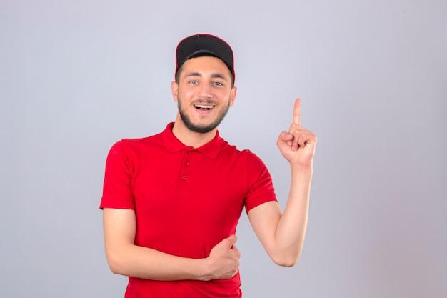 Jonge leveringsmens die rood poloshirt en glb draagt die vrolijk met vinger omhoog wijst over geïsoleerde witte achtergrond