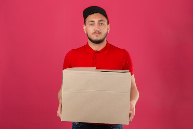 Jonge leveringsmens die rood poloshirt en glb draagt die zich met kartondoos met ernstig gezicht over geïsoleerde roze achtergrond bevinden