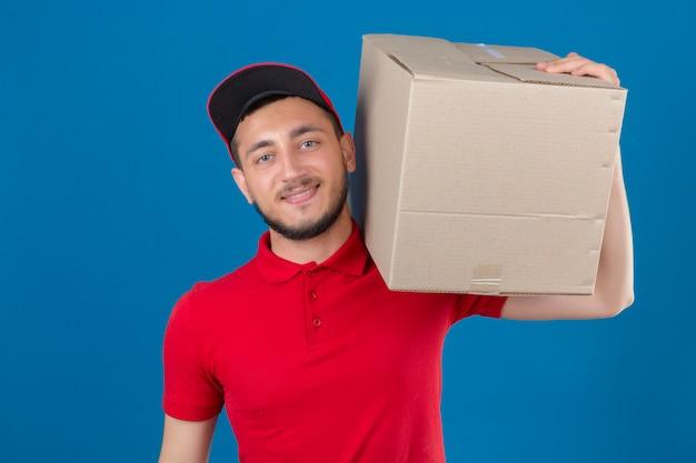 Jonge leveringsmens die rood poloshirt en glb draagt die zich met kartondoos op schouder bevindt die camera over geïsoleerde blauwe achtergrond bekijkt glimlachen