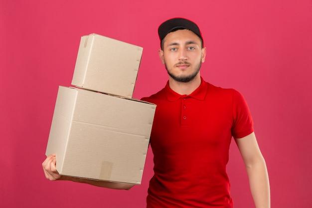 Jonge leveringsmens die rood poloshirt en glb draagt die zich met kartondozen bevinden die camera met ernstig gezicht over geïsoleerde roze achtergrond bekijken