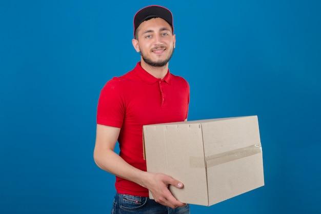Jonge leveringsmens die rood poloshirt en glb draagt die zich met kartondozen bevinden die camera met vriendschappelijke glimlach over geïsoleerde blauwe achtergrond bekijken
