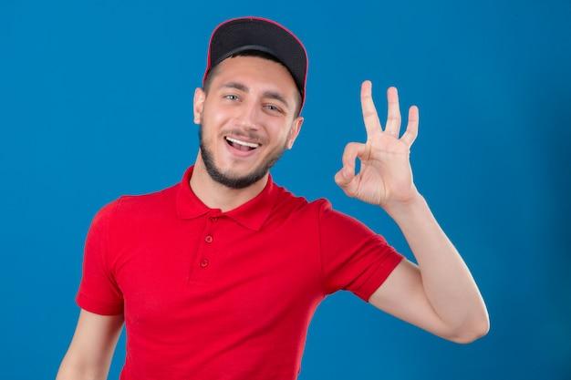 Jonge leveringsmens die rood poloshirt en glb dragen die vrolijk glimlachen doet ok teken over geïsoleerde blauwe achtergrond