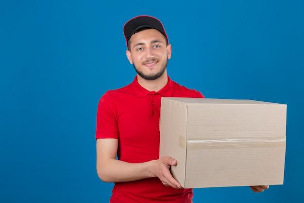Jonge leveringsmens die rood poloshirt en glb dragen die zich met karton bevinden die vriendschappelijk camera over geïsoleerde blauwe achtergrond bekijken glimlachen