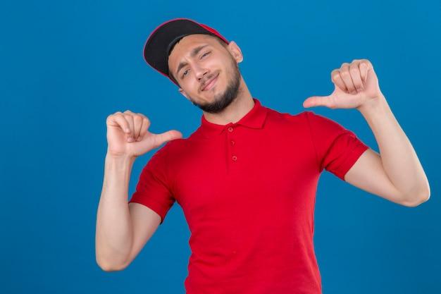 Jonge leveringsmens die rood poloshirt en pet draagt die camera bekijkt die vrolijk trots en zelfvoldaan glimlacht over geïsoleerde blauwe achtergrond