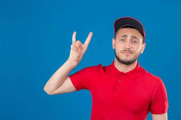 Jonge leveringsmens die rood poloshirt en pet draagt die rotssymbool doet die zelfverzekerd over geïsoleerde blauwe achtergrond kijkt