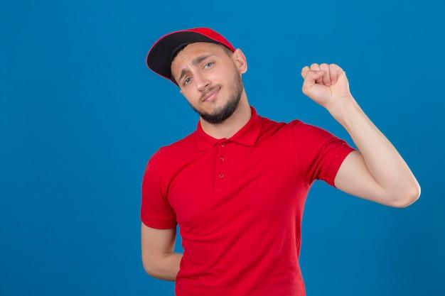 Jonge leveringsmens die rood poloshirt en pet draagt die vuist opheft na een concept van de overwinningswinnaar over geïsoleerde blauwe achtergrond