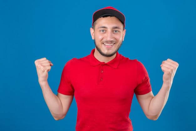Jonge leveringsmens die rood poloshirt en pet draagt die zich met opgeheven vuisten bevinden die op zoek zeker winnaarconcept over geïsoleerde blauwe achtergrond kijken