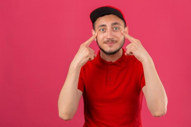 Jonge leveringsmens die rood poloshirt en pet draagt die zijn ogen richten die camera over geïsoleerde roze achtergrond glimlachen bekijken