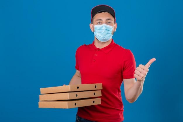 Jonge leveringsmens die rood poloshirt en pet in beschermend medisch masker dragen die zich met stapel pizzadozen bevinden die duim over geïsoleerde blauwe achtergrond tonen
