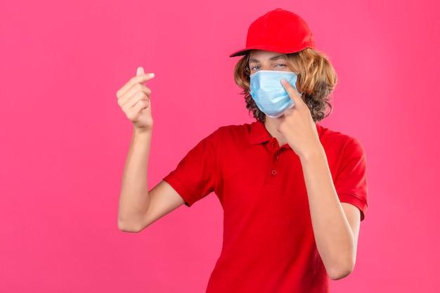 Jonge leveringsmens die rood poloshirt en pet in medisch masker draagt die een geldgebaar doet die zelfverzekerd over geïsoleerde roze achtergrond kijkt