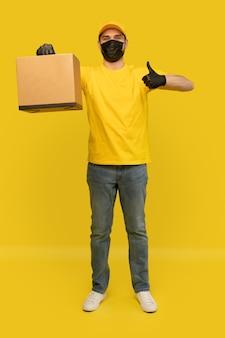 Jonge leveringsmens in gele t-shirt, masker, handschoenen met geïsoleerde doos