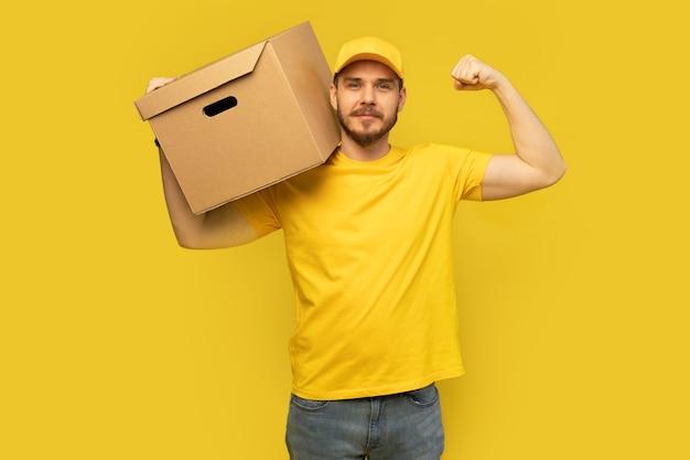 Jonge leveringsmens in gele t-shirt met doos die over geel wordt geïsoleerd