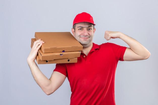 Jonge leveringsmens in rood poloshirt en glb-de dozen die van de holdingspizza vuist opheffen die zeker winnaarconcept over geïsoleerde witte muur glimlachen