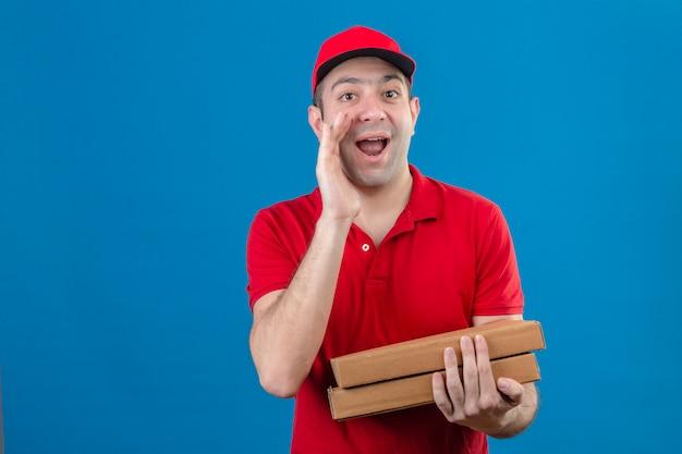 Jonge leveringsmens in rood poloshirt en glb die pizzadozen houden die naam schreeuwen die iemand met hand dichtbij mond zoeken die vrolijk over geïsoleerde blauwe muur glimlachen