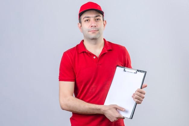 Jonge leveringsmens in rood poloshirt en glb die zich met klembord in handen bevinden die camera met glimlach over geïsoleerde witte achtergrond bekijken