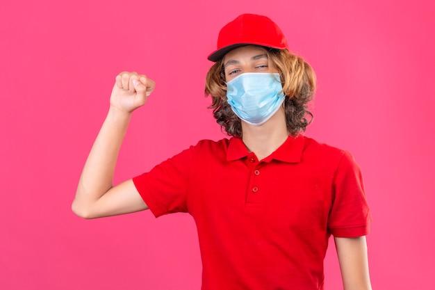 Jonge leveringsmens in rood uniform die medisch masker draagt dat vuist trots en zelfverzekerd winnaarconcept opheft dat zich over geïsoleerde roze achtergrond bevindt