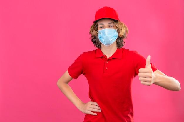 Jonge leveringsmens in rood uniform die medisch masker draagt die camera bekijkt die vrolijk glimlachen toont die over geïsoleerde roze achtergrond omhoog glimlacht