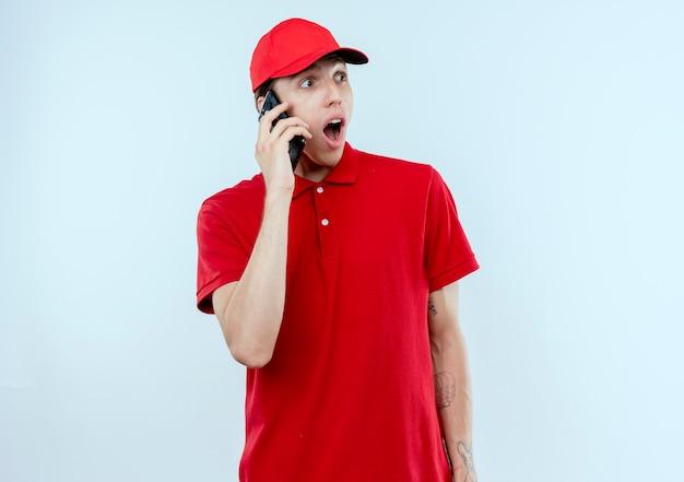 Jonge leveringsmens in rood uniform en glb die op mobiele telefoon spreken geschokte uitdrukking die zich over witte muur bevindt