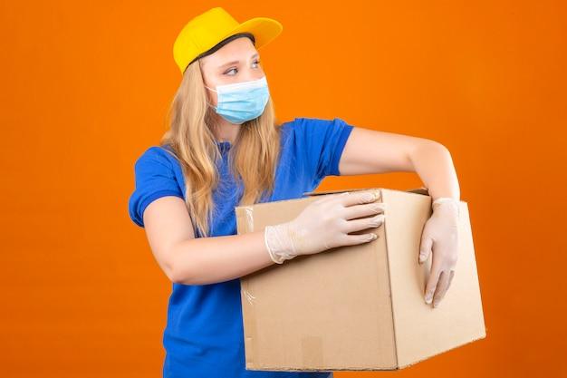 Jonge leveringsvrouw die blauw poloshirt en gele pet in medisch beschermend masker dragen die grote kartondoos houden die opzij over geïsoleerde donkergele achtergrond kijken