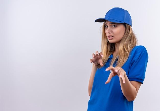 Jonge leveringsvrouw die blauw uniform en pet draagt die tijgergebaar toont