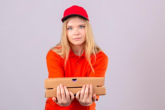 Jonge leveringsvrouw die in oranje poloshirt en rood glb camera bekijken die zich uit een stapel pizzadozen over geïsoleerde witte achtergrond uitstrekken