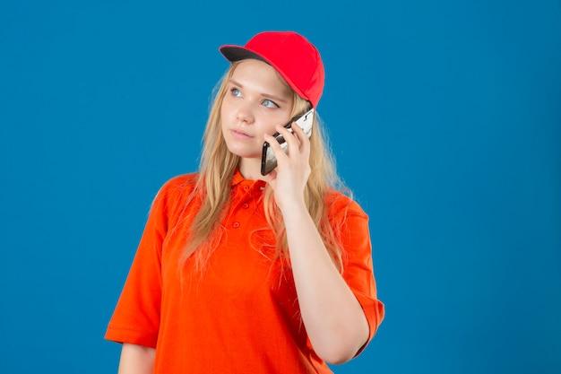 Jonge leveringsvrouw die oranje poloshirt en een rode pet draagt die op mobiele telefoon met zelfverzekerde blik over geïsoleerde blauwe achtergrond spreekt