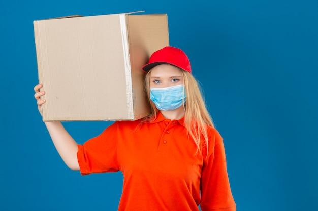 Jonge leveringsvrouw die oranje poloshirt en rode pet in medisch beschermend masker draagt ?? die zich met kartondoos op schouder bevindt die camera over geïsoleerde blauwe achtergrond bekijkt