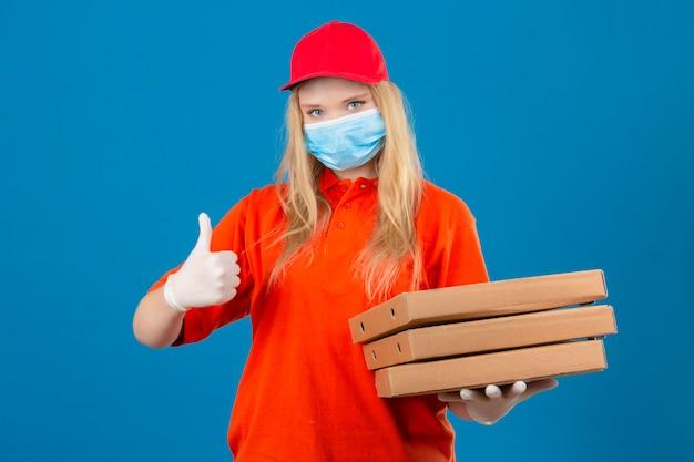 Jonge leveringsvrouw die oranje poloshirt en rode pet in medisch beschermend masker draagt met een stapel pizzadozen die duim tonen die over geïsoleerde blauwe achtergrond glimlachen