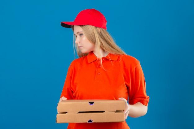 Jonge leveringsvrouw die oranje poloshirt en rood glb draagt die zich zijwaarts pizzadozen over geïsoleerde blauwe achtergrond houden