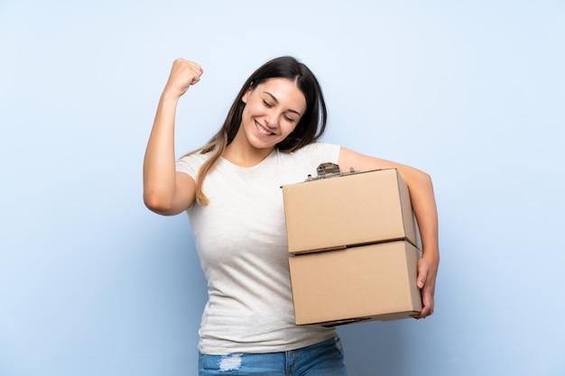 Jonge leveringsvrouw die over blauwe bakstenen muur een overwinning viert