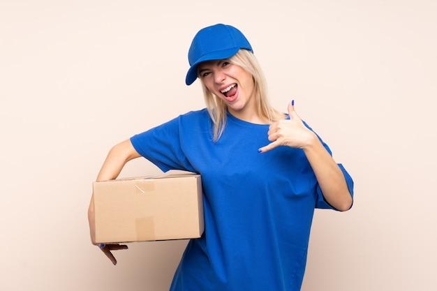 Jonge leveringsvrouw die over geïsoleerde muur telefoongebaar maken