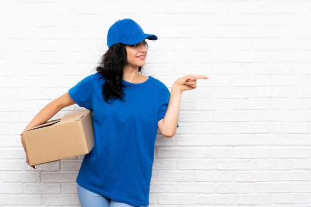 Jonge leveringsvrouw die over witte bakstenen muur aan de kant richt om een product te presenteren