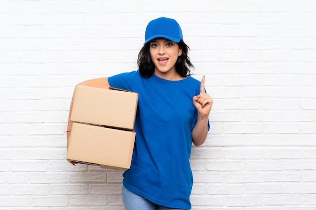 Jonge leveringsvrouw die over witte bakstenen muur een groot idee benadrukt