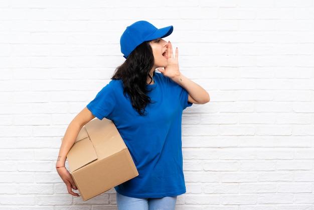 Jonge leveringsvrouw die over witte bakstenen muur met wijd open mond schreeuwen