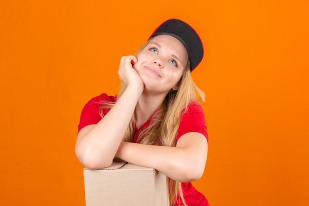 Jonge leveringsvrouw die rode poloshirt en pet draagt ?? glimlachend wachtend met hand op de wang terwijl het ondersteunen met een andere gekruiste hand dromerige blik over geïsoleerde oranje achtergrond