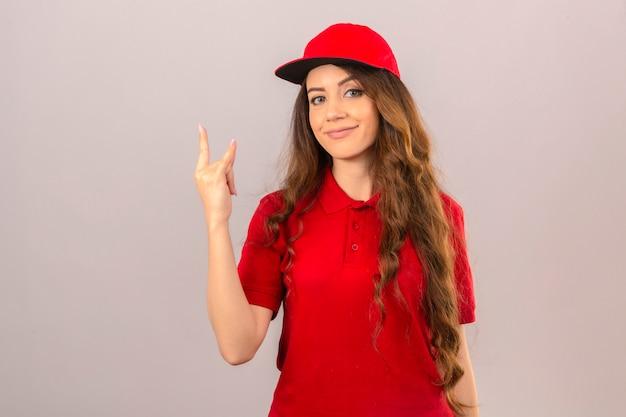 Jonge leveringsvrouw die rode poloshirt en pet draagt jonge leveringsvrouw die rode poloshirt en pet draagt ?? die zich met pizzadozen bevindt die vriendelijk glimlachen over geïsoleerde witte achtergrond over geïsoleerd