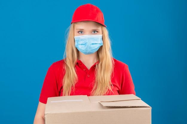 Jonge leveringsvrouw die rode poloshirt en pet in medisch beschermend masker draagt ?? dat zich met kartondozen bevindt die camera met ernstig gezicht over geïsoleerde blauwe achtergrond bekijken