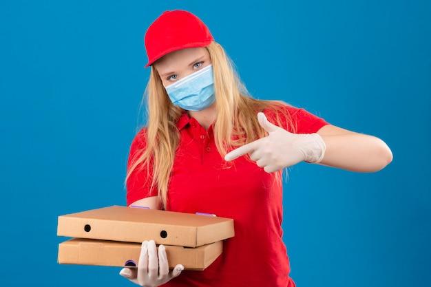Jonge leveringsvrouw die rode poloshirt en pet in medisch beschermend masker draagt ?? dat zich met pizzadozen met vinger naar hen richt die camera met ernstig gezicht over geïsoleerde blauwe rug bekijken