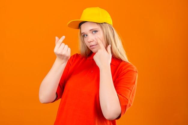 Jonge leveringsvrouw die rood poloshirt en geel glb dragen die geldgebaar doen die over geïsoleerde oranje achtergrond glimlachen