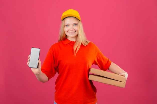 Jonge leveringsvrouw die rood poloshirt en geel glb dragen die pizzadozen houden die mobiele telefoon glimlachen die vriendschappelijk over geïsoleerde roze achtergrond glimlachen