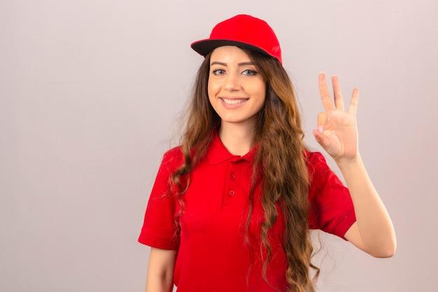 Jonge leveringsvrouw die rood poloshirt en glb dragen die vriendschappelijk glimlachen doet ok teken over geïsoleerde witte achtergrond Gratis Foto