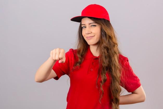 Jonge leveringsvrouw die rood poloshirt en glb dragen die vuistbuil tonen die vriendschappelijk over geïsoleerde witte achtergrond glimlachen