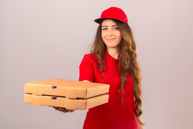 Jonge leveringsvrouw die rood poloshirt en glb dragen die zich met pizzadozen bevinden die hen aan klant geven die vriendelijk over geïsoleerde witte achtergrond glimlachen
