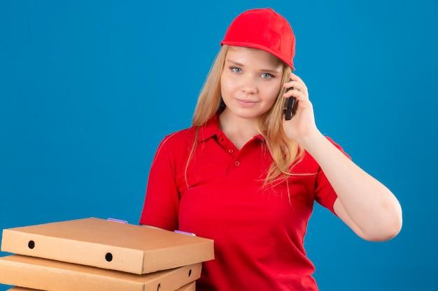 Jonge leveringsvrouw die rood poloshirt en glb dragen die zich met pizzadozen bevinden die op mobiele telefoon spreken die camera bekijken die zelfverzekerd over geïsoleerde blauwe achtergrond glimlacht