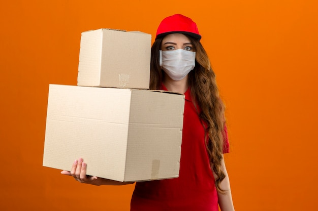 Jonge leveringsvrouw die rood poloshirt en glb in medisch beschermend masker draagt dat zich met kartondozen bevindt die over geïsoleerde oranje achtergrond vertrouwen kijken