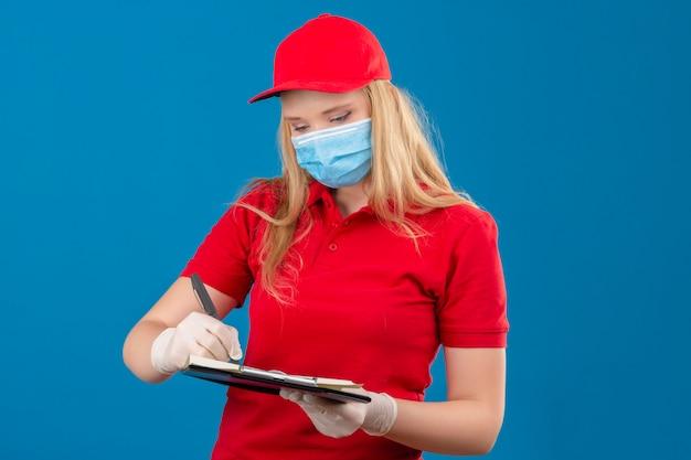 Jonge leveringsvrouw die rood poloshirt en glb in medisch beschermend masker dragen die zich met klembord het schrijven bevinden ernstig over geïsoleerde blauwe achtergrond kijken